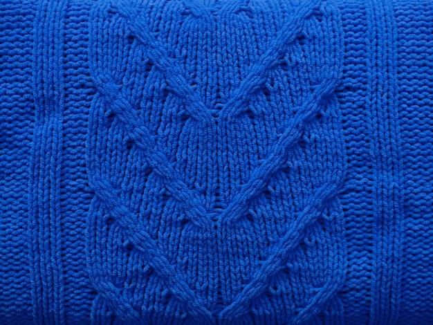 Вяжем текстуру из синей шерсти трикотажного полотна с кабельным узором в качестве фона. узор, обои, концепция для печати. классический синий цвет 2020 года