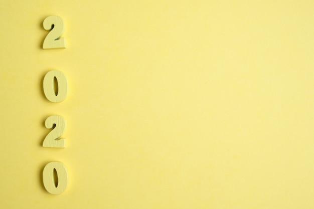 黄色の背景の木2020からの数字。今年のコンセプト。上面図。コピースペース。