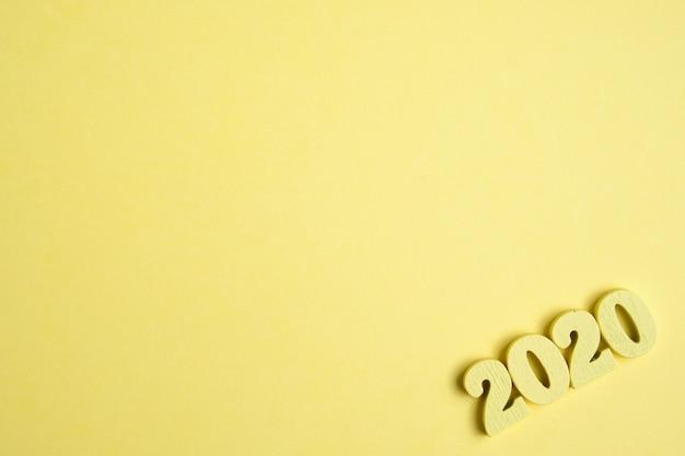 黄色の背景の右隅にある木材2020の図。今年のコンセプト。上面図。コピースペース。