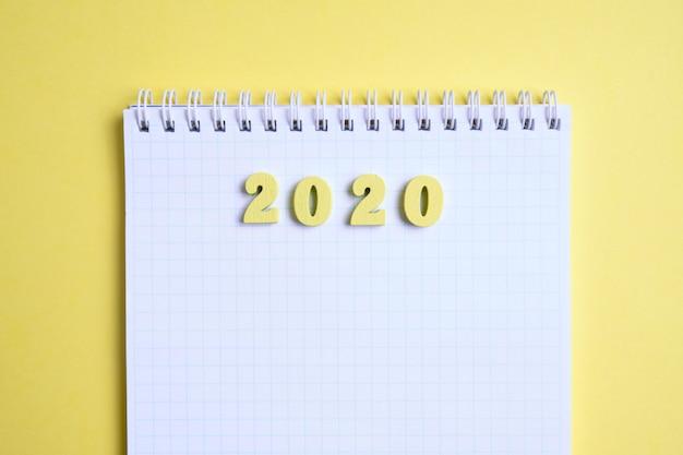 黄色の背景にノートの横にある木製の数字2020。上面図。