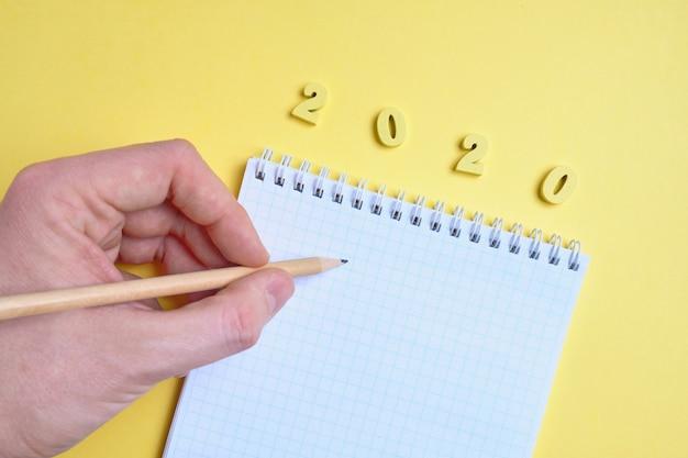 手は、黄色の背景にある木製の文字2020の隣のメモ帳の近くに鉛筆を持っています。上面図。