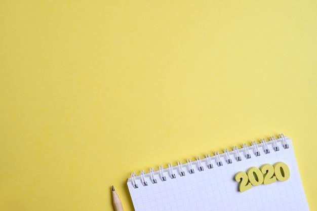 メモ帳の横にある鉛筆と黄色の背景に木製の数字2020。その年の新しいタスクを記録する概念。上面図。コピースペース。