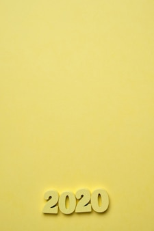 黄色の背景の右隅にある木材2020の図。今年のコンセプト。上面図。コピースペース。垂直。