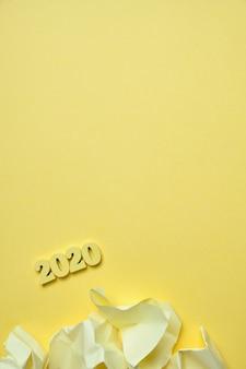 黄色の背景に木製の数字2020の横にあるしわくちゃのステッカー。上面図。垂直。コピースペース。