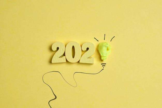 新しいアイデアのコンセプト。黄色の背景に2020の数字で抽象的な紙電球。上面図。