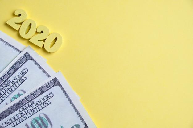 2020年に銀行のコンセプトで収益性の高い預金。黄色の背景にドルの横に木製の数字。上面図。コピースペース。
