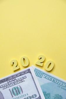 新しい年の通貨取引。ドルの横にある黄色の背景に木製の数字2020。上面図。コピースペース。