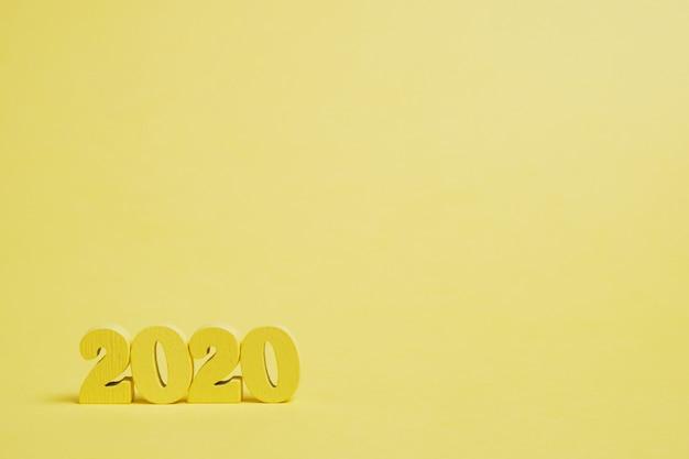 黄色の背景に木製の数字2020。コピースペース。