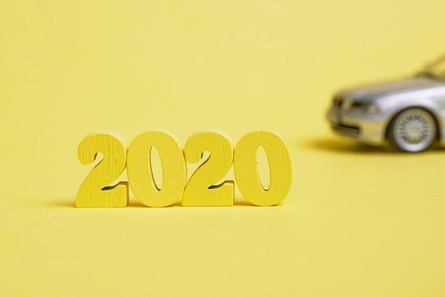 ぼやけた車で黄色の背景に木製の数字2020。