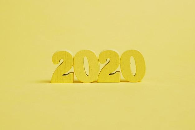 黄色の背景に木製の数字2020。