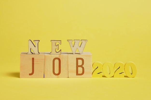 新しい仕事のコンセプト。黄色の背景に文字を持つキューブの横にある木製の番号2020。