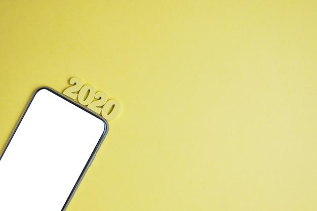 黄色の背景の左隅にある携帯電話の横にある木製の文字の2020年を抽象化します。上面図。コピースペース。