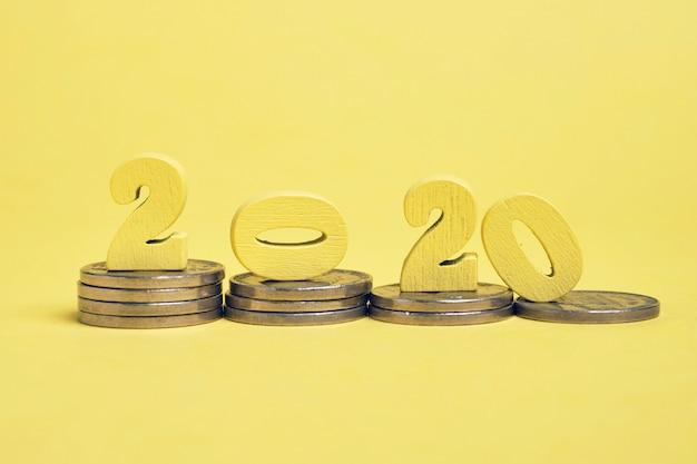コインのスタック上の木製フィギュア2020。新しい年の財政の安定の概念。