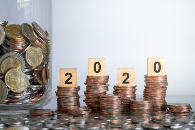 ビジネスと節約の概念のためのガラスの瓶にコインの山とコインスタックの2020年の木製ブロック数。