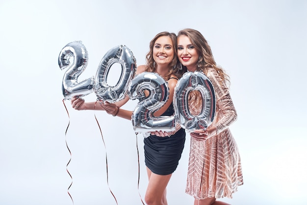 Счастливые молодые женщины в платьях с металлической фольгой 2020 шары на белом.