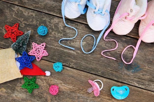 子供の靴とおしゃぶりの2020年新年書かれたひも。