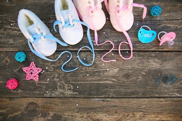 古い木製の背景に子供の靴とおしゃぶりのひもを書かれた2020年