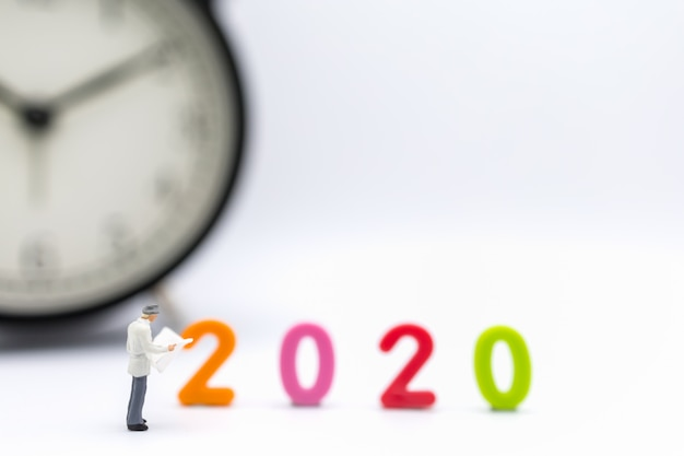 ビジネスマンミニチュアフィギュア立ち、2020年カラフルなプラスチック製の数字と時計で新聞を読む