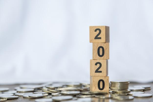 2020年、お金とビジネスコンセプト。コインの山に数木製ブロックグッズのスタックのクローズアップ