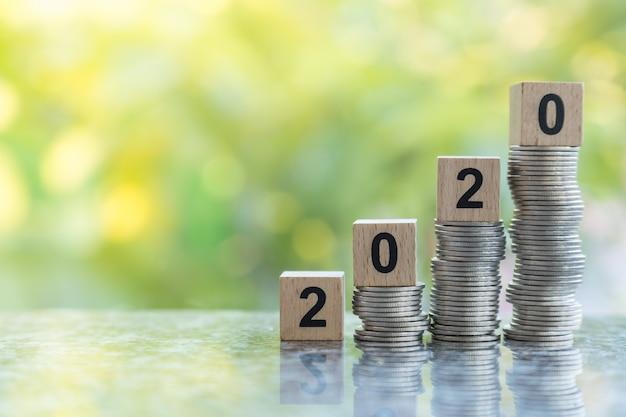 Крупный план игрушечного деревянного блока 2020 года на вершине нестабильной стопки монет с боке зеленых листьев природы