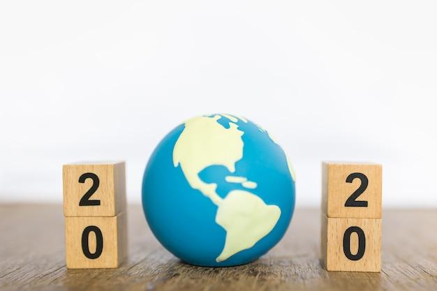2020年、グローバルおよびビジネスコンセプト。コピースペースを持つ木製のナンバーブロックとミニ世界グッズボールのスタックのクローズアップ