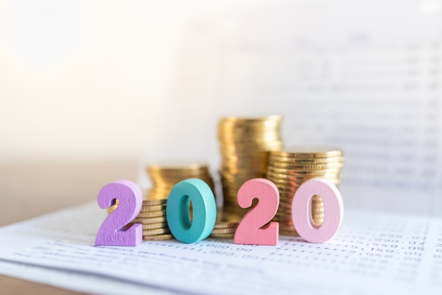 2020 новый год, бизнес, сбережения и планирование концепции. закройте вверх красочного деревянного номера на банковской книжке на предъявителя банка с стогом золотых монеток с космосом экземпляра.