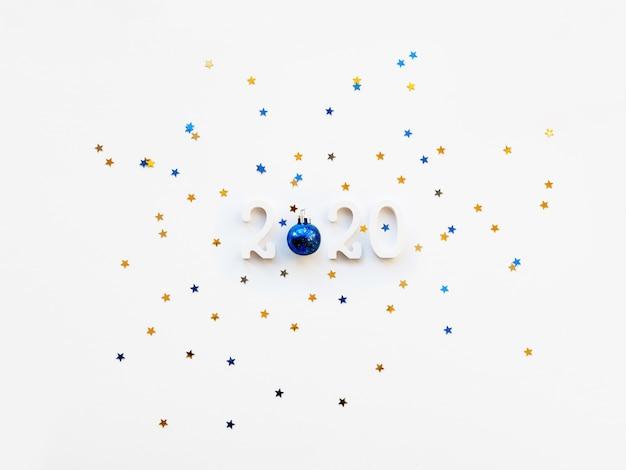 クリスマスと2020年の数字、光沢のある青いボール、金と青の星の紙吹雪。白い