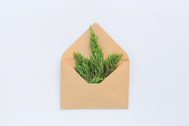 封筒、白のモミの枝でクリスマス組成。新年のコンセプト。グリーティングカード、冬休み、クリスマスのお祝い2020。フラット横たわっていた、トップビュー、コピースペース、モックアップ、テンプレート
