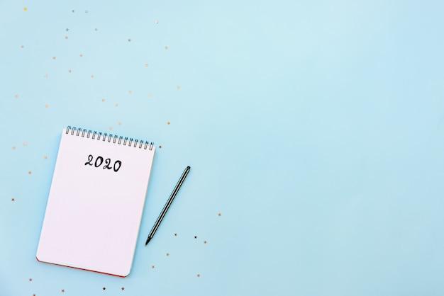 新しい2020年の計画またはウィッシュリストの準備ができている空のノートブックの平面図