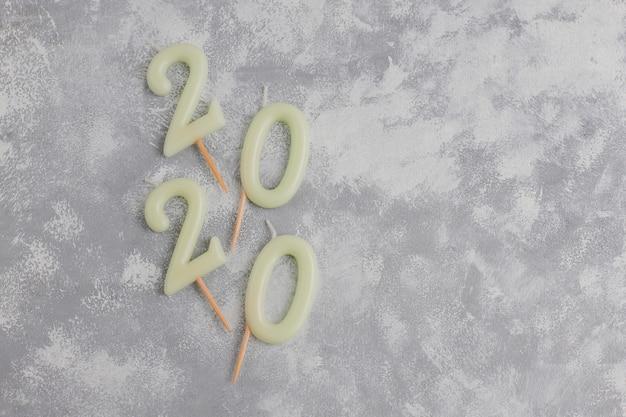 クリスマスの横にある新年のシンボルとしての数字2020の形のキャンドルは、灰色のテーブルに輝くキャンディーの形をしています。平面図、平置き