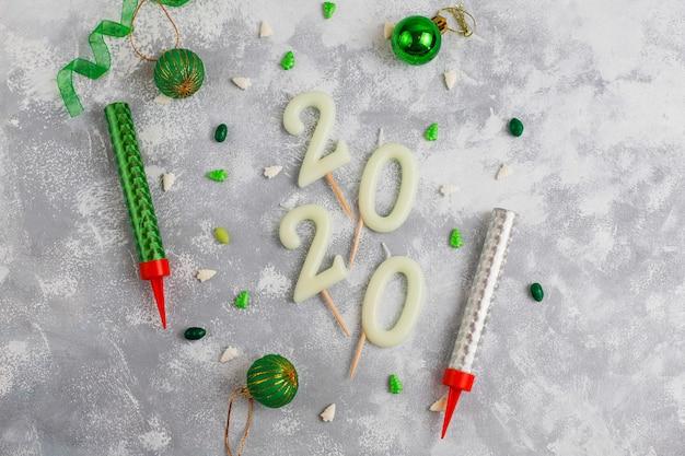 Свечи в форме цифр 2020 как символ нового года рядом с рождественскими сверкающими конфетами на сером столе. вид сверху, плоская планировка
