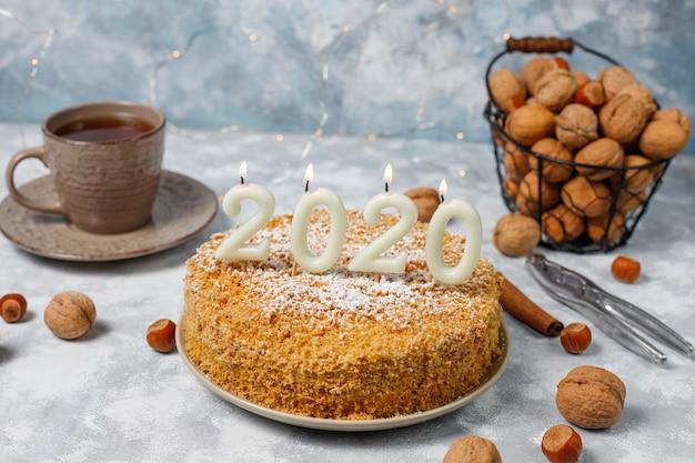 Морковный торт с 2020 свечами и чашкой чая на сером бетоне