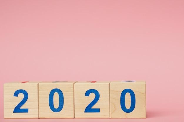新年2020コンセプト。ピンクのテーブルの番号を持つ木製ブロックキューブ