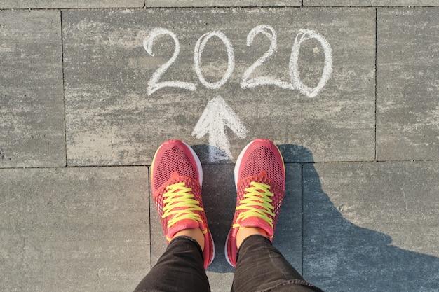 スニーカーで女性の足で灰色の歩道に書かれた2020年矢印