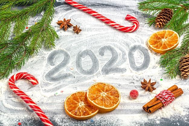 Рождественская плоская композиция. 2020 надпись и рамка еловые ветки, шишки, анис, корица и сушеные апельсины на столе муки. рождество, зимние каникулы, концепция нового года.