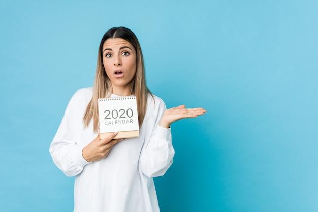 感銘を受けた2020年のカレンダーを保持している若い白人女性