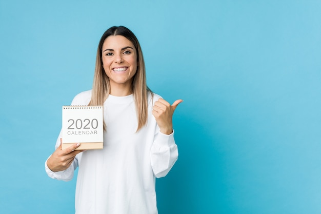 Молодая кавказская женщина держа календарь 2020 усмехаясь и поднимая большой палец руки вверх