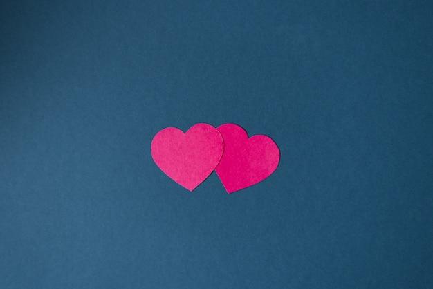 青色の背景、ペーパーアートのピンクの紙の心。 2020年の古典的な青い色。トレンド