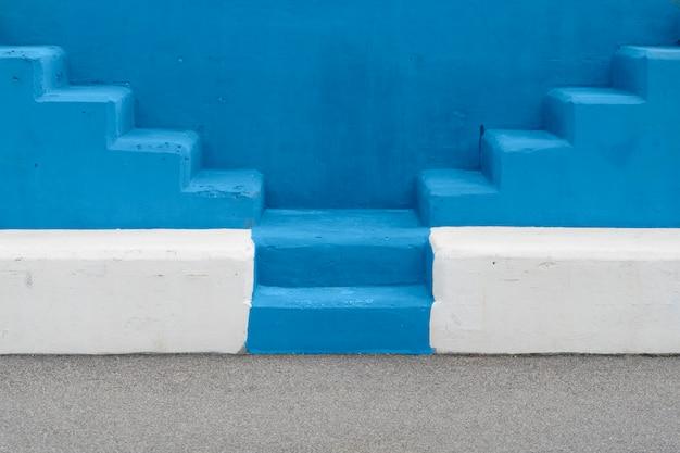 シンプルな背景テクスチャの階段。 2020年のトレンディな色。青い背景の屋外階段の選択的なビュー。シンプルなコンセプト。
