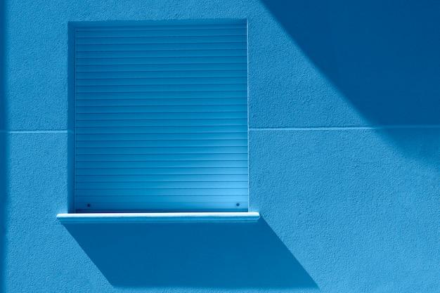 2020年の流行色。壁に太陽からの影とミニマリストの青い窓。家の側壁に掛かっている正方形の青い窓。