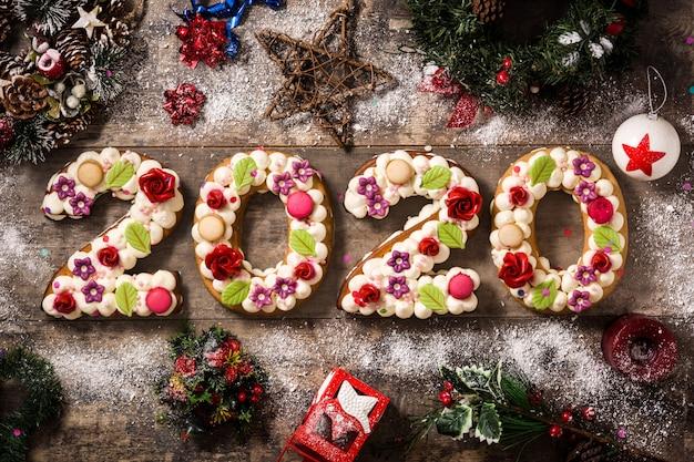 木製のテーブルに2020年のケーキとクリスマスの飾り。新年のコンセプト。