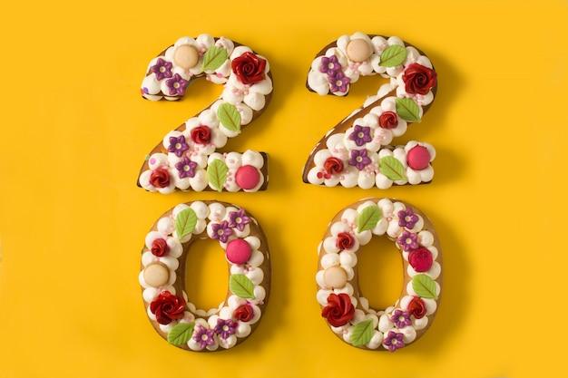 黄色の表面に2020年のケーキ
