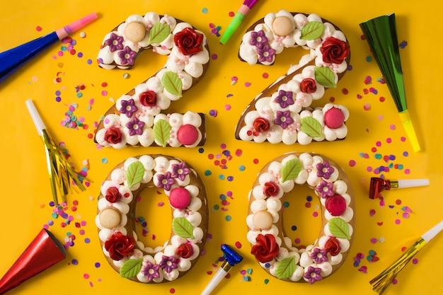 2020年のケーキと黄色の背景に分離された装飾品。新年のコンセプト。