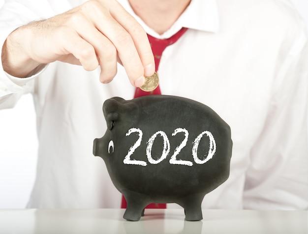 Бизнесмен кладет деньги в копилку с рисунком 2020 года