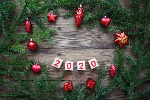 2020 в рамке из еловых веток и красных игрушек на деревянном фоне