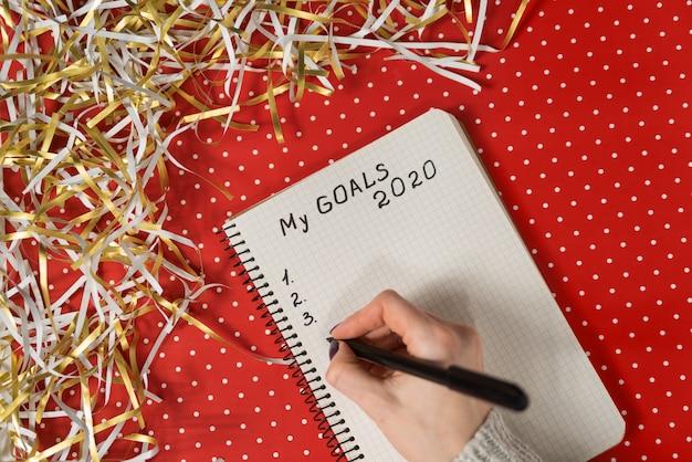 ノートブックに私の目標2020を書く女性の手