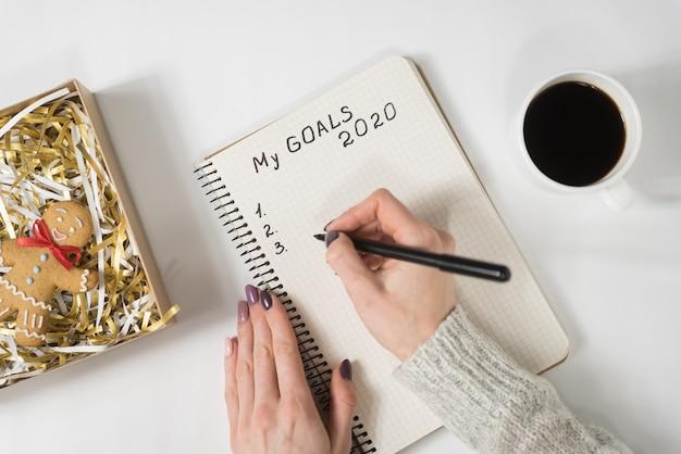 ノートブックに私の目標2020を書く女性の手。マグカップのコーヒーとジンジャーブレッド人、トップビュー