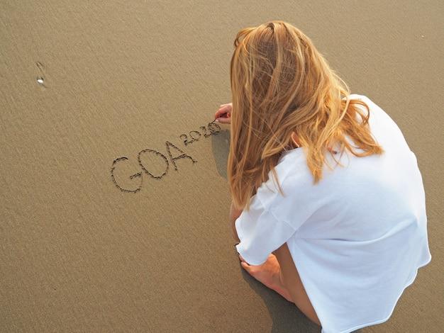 女の子は海に面した砂の上に座って、2020年のゴアの碑文を書きます