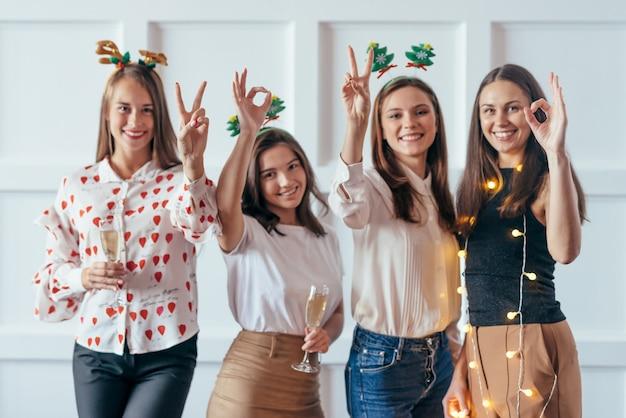 Друзья празднуют рождество или новый год на вечеринке, показывая жесты 2020.