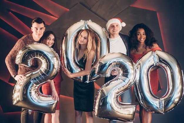 Счастливы и улыбаются. группа красивых молодых друзей с надувными номерами в руках празднует новый 2020 год
